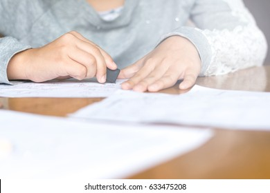 Portrait of adorable Asia kid girl doing boring homework with bored feeling at home. Female cute child using black rubber erase wrong answer written on paper. Asian students doing test exam math.