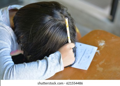 Portrait of adorable Asian kid girl doing examination homework with stress feeling at school. Female cute child asleep on paper. Asian students sleeping while practice math subject for test at home.