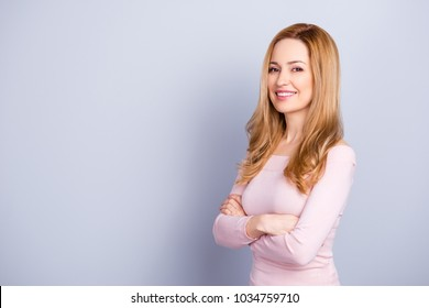 Portrait of adorable attractive confident mature cheerful woman with long blonde wavy hair wearing light pink blouse keeping arms crossed isolated on gray background