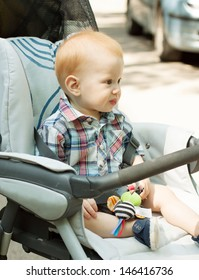 Portrait of adorable baby boy sitting in stroller