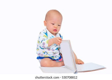 Portrait of an adorable baby boy sitting up and looking at a book, isolated on white, Toddler boy try to read a book, 11 months pretty child playing with open book, turn over the pages with copy space