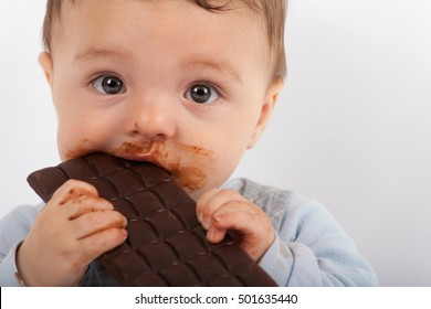 Portrait of an adorable baby eating chocolate