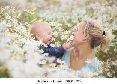 Portrait of adorable baby with flowers in chamomile field. Mother holding child and walking on wild flowers meadow.