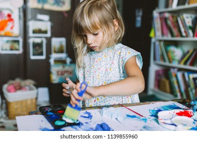 Portrait of adorable baby girl painting  at home 
