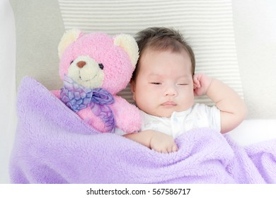 Portrait of adorable baby girl sleeping on the bed with bear doll.