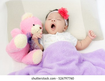 Portrait of adorable baby girl wake up on the bed with bear doll with copy space