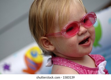 A portrait of an adorable baby girl wearing pink sunglasses.