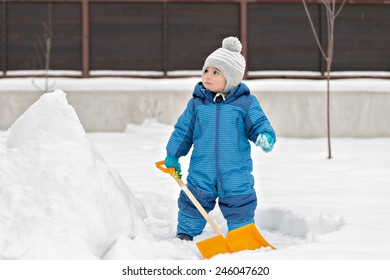 Portrait of adorable baby holding snow shovel