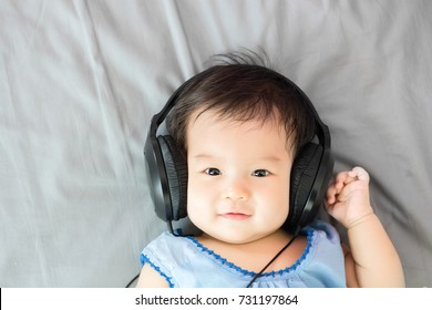 Portrait of adorable baby lying on the bed with headphone, indoors