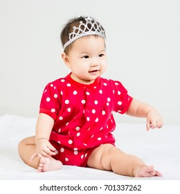 Portrait of adorable  baby sitting on a white floor with crown