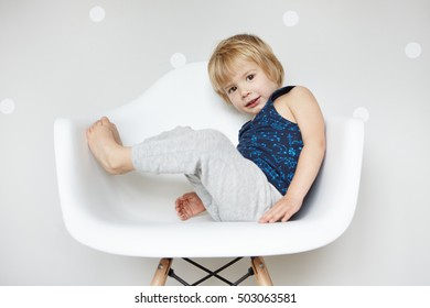 Portrait of adorable barefooted child with blond hair dressed in gray pants and sleeveless shirt enjoying infantine pastimes indoors, sitting on white chair, looking happy and joyful. Horizontal