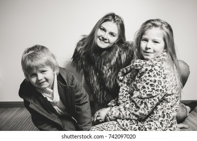 Portrait of adorable beautiful young family looking lovely in winter style clothing over light background. Healthy, emotional, peaceful joyful happiness lifestyle