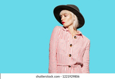 Portrait of adorable blonde model fashionably dressed in striped dress and hat. Stylish caucasian woman posing indoors on blue background. Modern fashion concept
