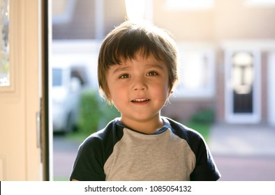 Portrait of adorable boy standing next to the front door with smiling face, Preschool boy back from school with a happy face, Cute little boy with a bit of dirty face from playing outside with friends