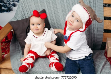 Portrait of adorable brother with his little baby sister wearing Christmas clothes sitting on knit blanket on bench.