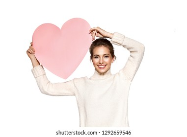 Portrait of adorable brunette female holding paper pink heart. Lovely young woman standing in studio in pretty pullover. Copy space in right side. Isolated on white background