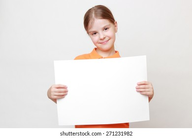 Portrait of adorable caucasian little girl with white blank for advertisment