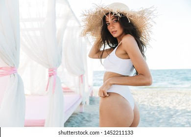 Portrait of adorable caucasian woman in swimsuit and straw hat standing over beach bed by seaside in summer resort