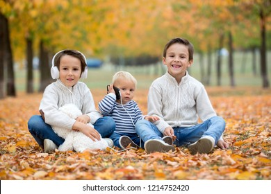 Portrait of adorable children, brothers, in autumn park, listening music and playing on mobile phone and with teddy bear, autumntime