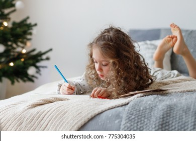 Portrait of adorable curly girl spends free time on bed, makes Christmas card for parents, writes wishes and draws pictures, has concentrated look, being obidient kid. New Year and children concept.
