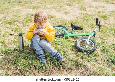 Portrait of Adorable cute boy resting and drinking tea from a thermos in the beauty autumn park.