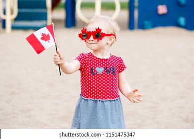 Portrait of adorable cute little blonde Caucasian baby toddler girl holding Canadian flag. Female child wearing funny maple leaves sunglasses celebrating Canada Day