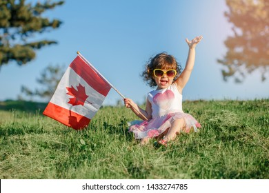 Portrait of adorable cute little Caucasian baby toddler girl sitting on green grass in park outside and holding waving large Canadian flag. Kid child citizen celebrating Canada Day on 1st of July.