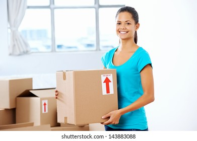 portrait of adorable girl moving into new home holding box