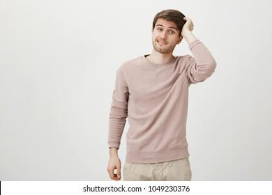 Portrait of adorable handsome caucasian man with bristle scratching head while being puzzled or clueless, standing against gray background. I forgot to buy milk, but I promise to do it next time