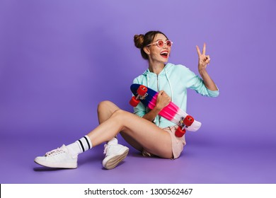 Portrait of adorable hipster girl in streetwear smiling and sitting on floor with skateboard isolated over violet background in studio