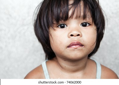 Portrait of an adorable, impoverished girl from the Philippines against wall.