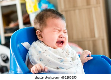 Portrait of adorable infant baby girl sitting on the chair and crying while eating baby food