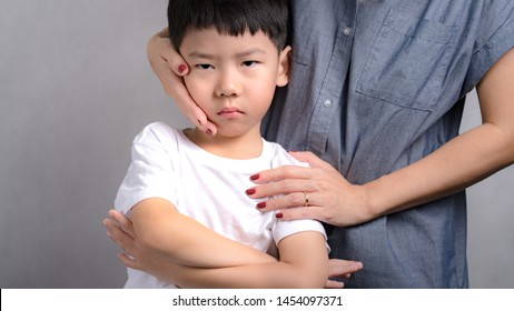 Portrait of adorable innocence little asian boy (3-6 years old) frown face expression feeling unhappy, disappointed while his Mom comforting, soothing him with love and care. Parenting child concept.