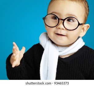 portrait of adorable kid gesturing doubt against a blue background