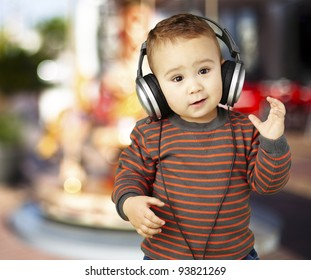 portrait of an adorable kid with headphones listening to music against a carousel background