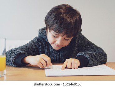 Portrait of adorable kid sitting alone doing homework with happy face, Cute child boy using rubber rubbing wrong word written on paper. Students doing spelling test at home.Homeschooling concept