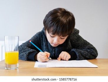 Portrait of adorable kid sitting alone doing homework with happy face, Cute child boy using pencil writing on white paper. Students doing spelling test at home.Homeschooling concept