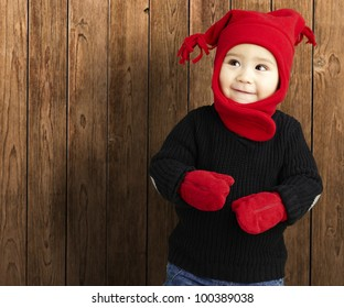portrait of an adorable kid smiling wearing winter clothes against a wooden background