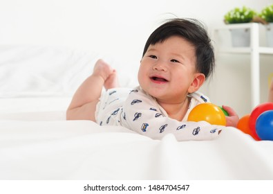 Portrait of Adorable laughing boy baby on white bed sheet in a bedroom. innocent happiness in playing time.Baby laughing when playing colorful ball. Expression of funny baby. innocent concept