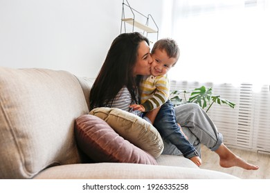 Portrait of adorable little boy sitting on his mom's laps and smiling. Mother showing love to her toddler with a kiss on a cheek. Close up, copy space, background.