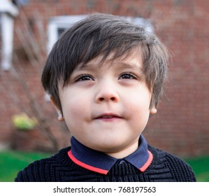 Portrait  of adorable little boy standing outside and looking up sky, Kid boy hair style with black sweaters