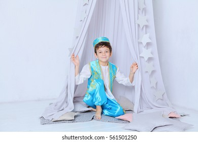 Portrait of adorable little boy wearing Turkish traditional national blue costume and cap sitting in white decorative hovel with stars on pillows and smiling to the camera. Traditions and hospitality