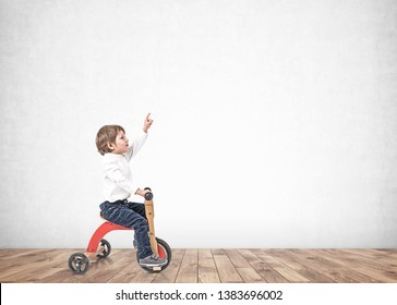 Portrait of adorable little boy in white shirt and jeans riding tricycle and pointing upwards. Concrete wall background. Mock up