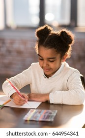 Portrait of adorable little elementary school student holding pencil and doing homework