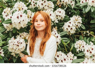Portrait of adorable little girl of 8-9 year old . Red-haired sweet young girl playing in spring garden