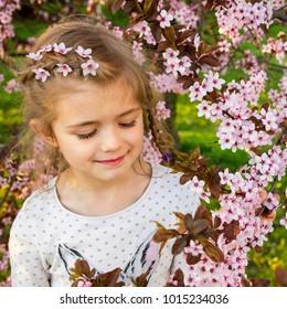 Portrait of adorable little girl in blossom garden in spring