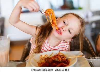 Portrait of adorable little girl eating spaghetti for a lunch at restaurant