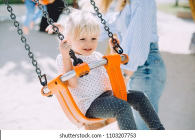 Portrait of adorable little girl having fun on swing at playground