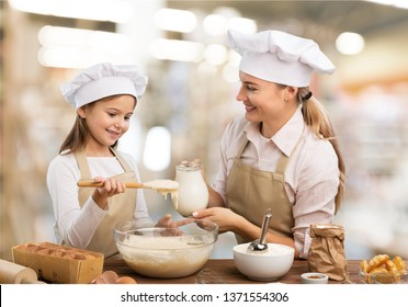 Portrait of adorable little girl and her mother baking together