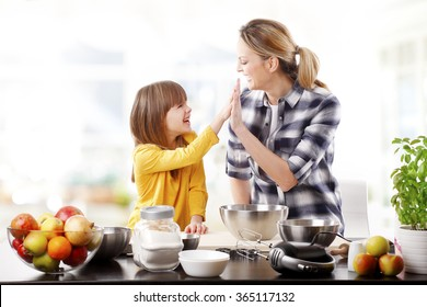 Portrait of adorable little girl and her mother baking together at home. Happy mom giving high five to her cutie daughter.